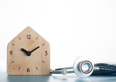 Wooden clock with stethoscope on blue background. Standard-Bild - 132606756