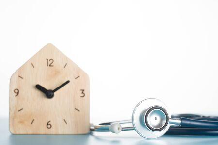 Wooden clock with stethoscope on blue background. Standard-Bild - 132831832