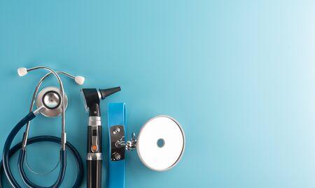 Otoscopio con stetoscopio e specchio riflettore su sfondo blu.