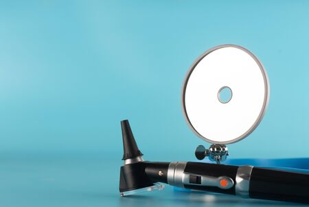 Otoscope with reflector mirror on blue background in health care concept. Standard-Bild - 132011329