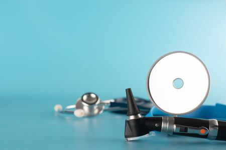 Otoscope with stethoscope and reflector mirror on blue background. 免版税图像 - 132010623