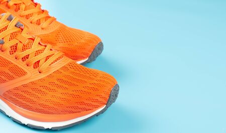 Orange sport shoes on a blue background. Concept for good health. Standard-Bild - 133598572