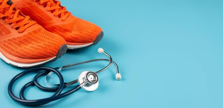 Orange sports shoes and stethoscope on the blue background. Concept exercise for good health. Standard-Bild - 133598618
