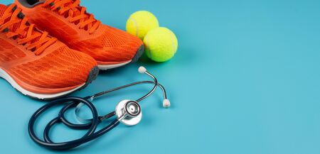 Orange sports shoes and stethoscope on the blue background. Concept exercise for good health. Standard-Bild - 133598625