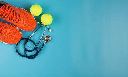 Orange sports shoes and stethoscope on the blue background. Concept exercise for good health. Standard-Bild - 133598629