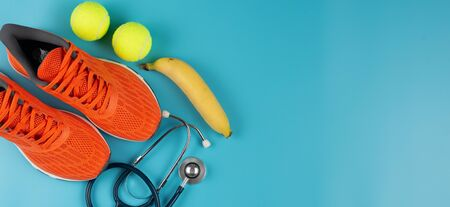 Orange sports shoes and stethoscope on the blue background. Concept exercise for good health. Standard-Bild - 133598638