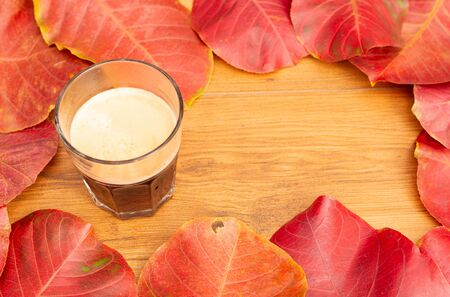 A cup of coffe with autumn leaf background. Standard-Bild - 133598704