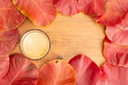 A cup of coffe with autumn leaf background. Standard-Bild - 133598713