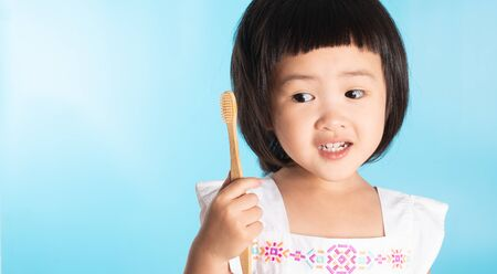 Cute Asian girl holding a toothbrush to clean her teeth on a blue background and copy space.