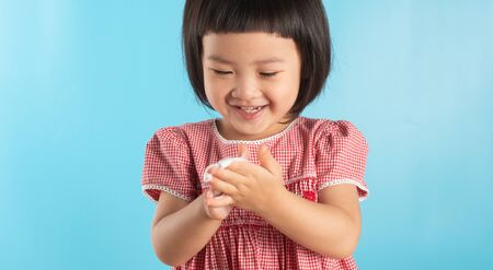 Cute Asian girl washing hands with soap bubbles to kill bacteria COVID - 19 for good health with fun and happiness. With copy space.