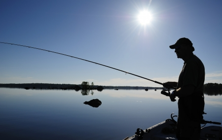 freshwater fishing: Angler shadow in morning sun Stock Photo