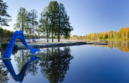 Autumn lake landscape with blue water slide  photo