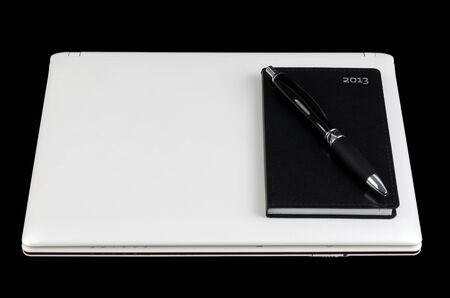 White laptop with pocket calendar and pen isolated on black background photo