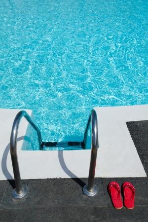 Red flip flops near tropical pool photo