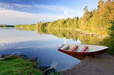 Idyllic september lake landscape with red rowboat photo