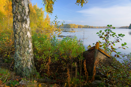 Old wooden boat on autumn lake coast photo