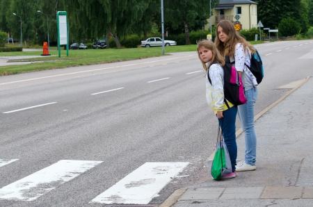 ni�os estudiando: Chicas buscan los coches antes de cruzar la calle