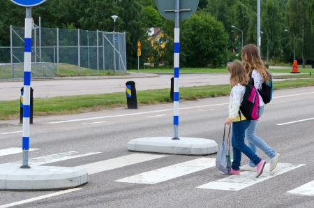 Girls crossing the street on the way to school  Banque d'images