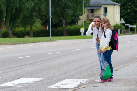 Mother teach daughter about safety rules before crossing the street on the school way  Standard-Bild