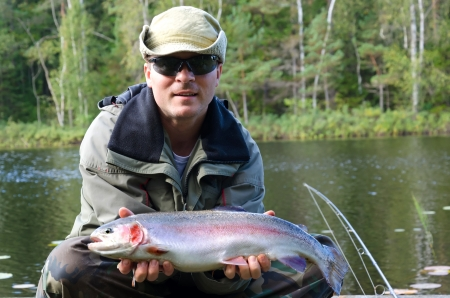 Happy angler with rainbow trout fishing trophy