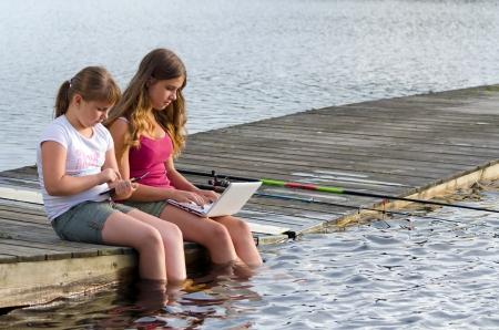 Girls choose social media instead fishing  Stock Photo