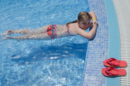 Girl child relaxing in tropical pool  photo