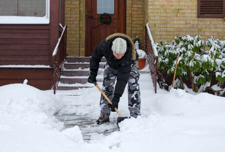 anomalies: Man removing snow in front of his house