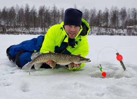 Happy angler with winter pike trophy fish photo