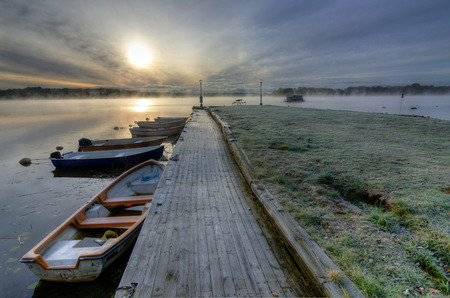 Small boat harbor in cold autumn morning photo