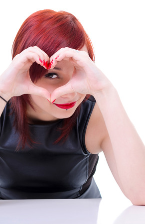 Attractive girl looking through hands heart photo
