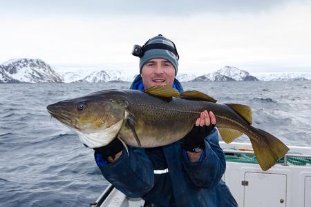 Happy angler with huge cod fish photo
