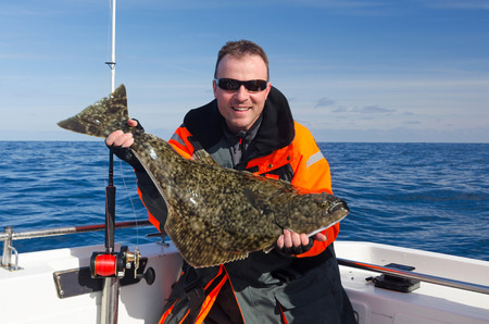 Happy angler with halibut fish Banque d'images