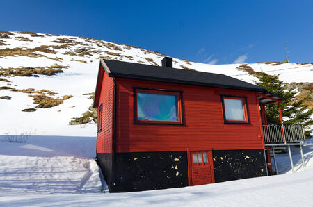 Typical Norwegian red house on the mountainside photo