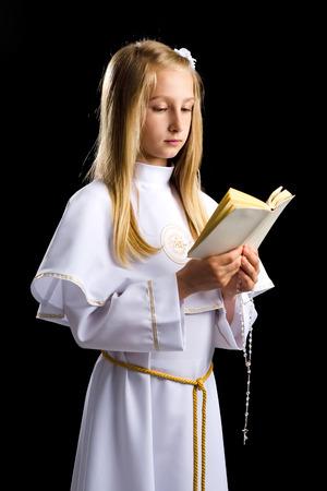 Meisje Heilige Bijbel voor de eerste communie lezen