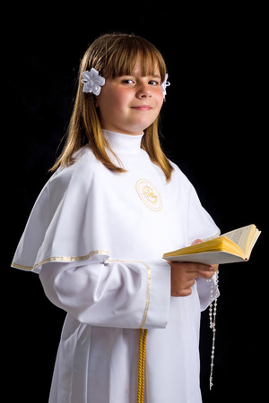 Portrait of smiling young brunette girl in first communion time photo