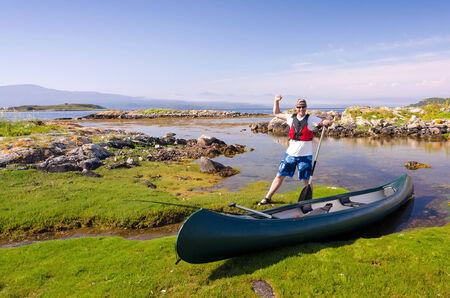 Happy canoe angler in wild nature photo