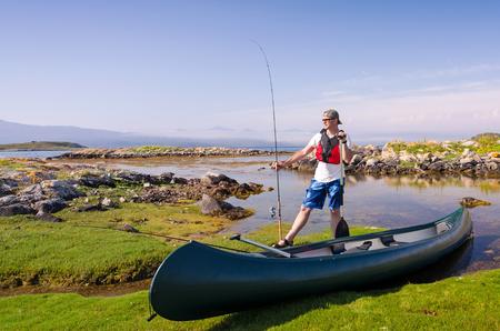 Canoe angler in Norwegian fjord scenery Stock Photo