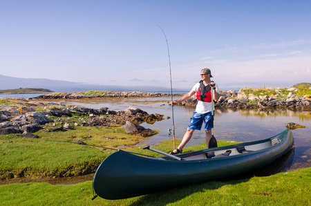 Canoe angler in Norwegian fjord scenery Banque d'images