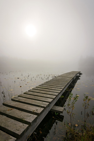 Wooden bridge in foggy scenery photo