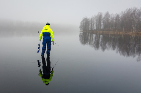 Ice fishing angler with reflection Standard-Bild