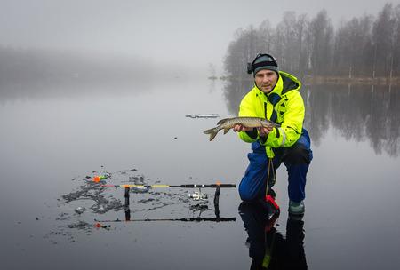 Men fishing pikes on ice photo