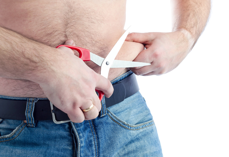 Man try to cut out fat stomach skin Stock Photo