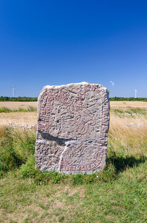 rune: Ancient rune stone with modern wind turbines in background