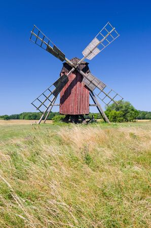 Red wooden windmill on the summer field Stockfoto