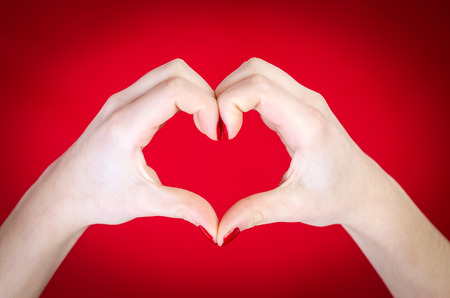 making love: Hands heart isolated on red background Stock Photo