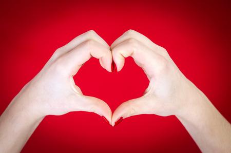 haciendo el amor: Manos del corazón aislado en fondo rojo