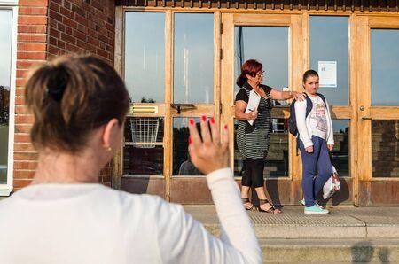 waving: Waving goodbye to upset schoolgirl