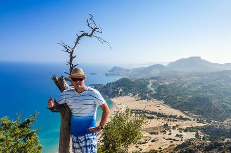 tsampika: Man on Tsambika mountain with beach background Stock Photo