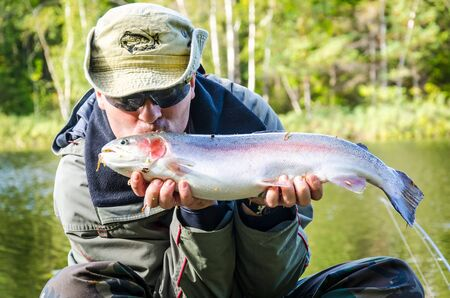 desired: Happy angler with desired trout fishing trophy