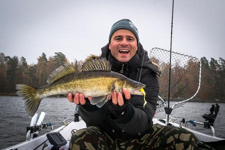barca da pesca: Pescatore estremamente felice con il pesce autunno walleye Archivio Fotografico